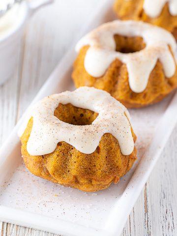 two mini pumpkin spice bundt cakes on a white plate