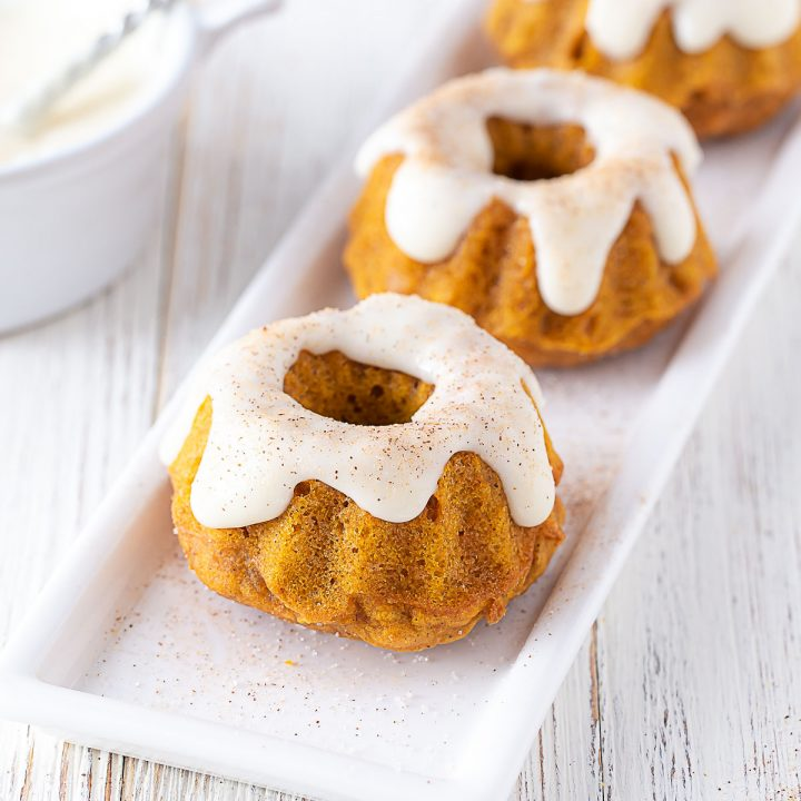 two mini pumpkin spice bundt cakes on a white plate