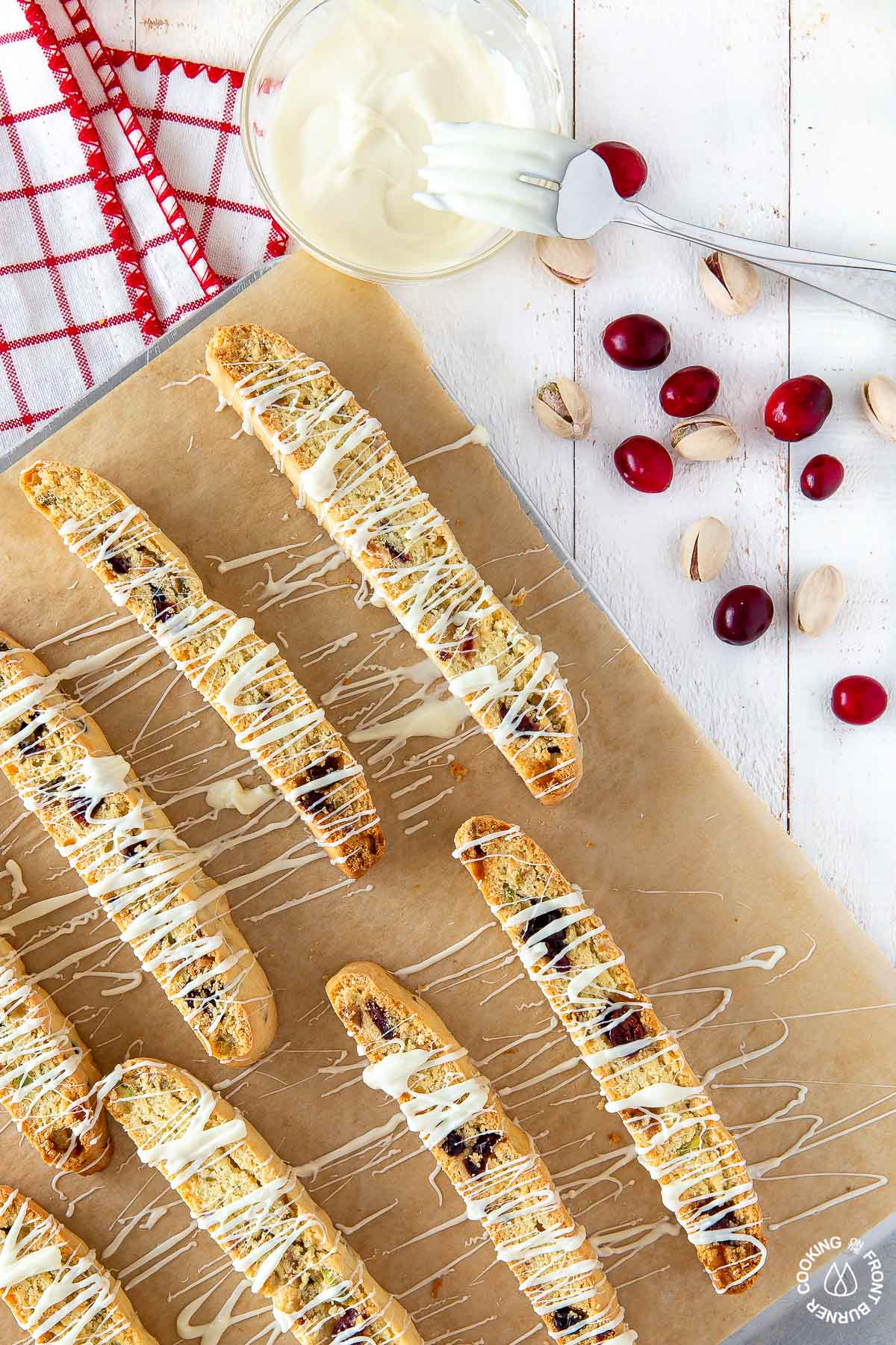 cranberry pistachio biscotti drizzled with white chocolate on a cookie sheet