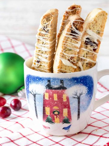 4 cranberry pistachio biscotti standing in a mug on a towel