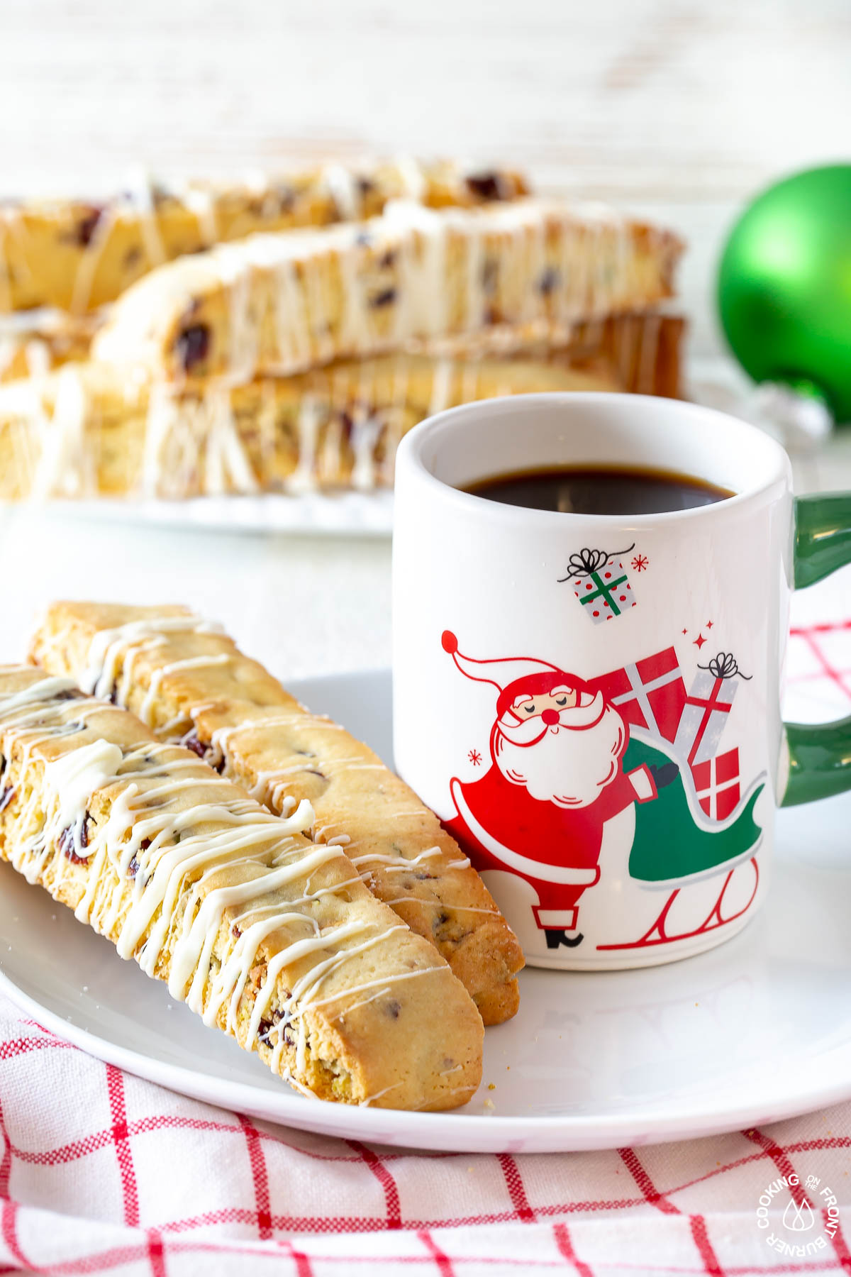 a cup of coffee with two cranberry pistachio biscotti on a plate