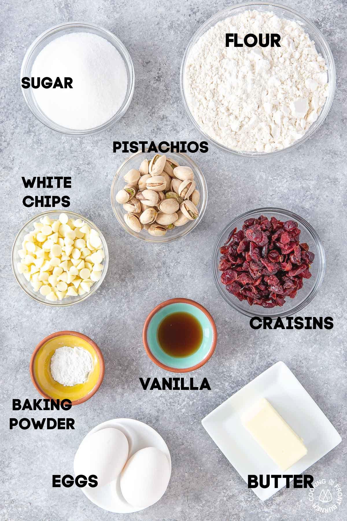 bowls of sugar, flour, pistachios, white chocolate chips, craisins, vanilla, baking powder, butter