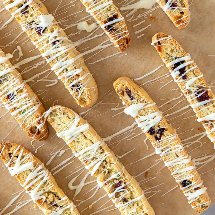 cranberry pistachio biscotti on parchment paper drizzled with white chocolate