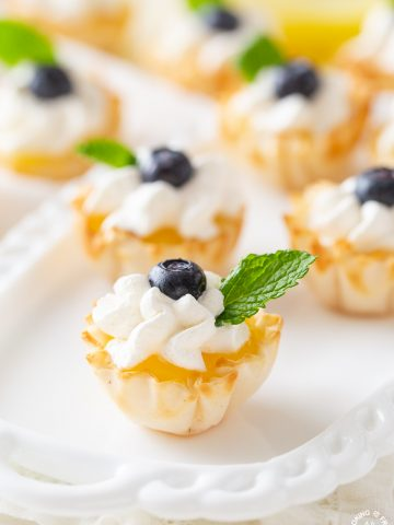 a phyllo cup with lemon curd topped with whipped cream and sprig mint