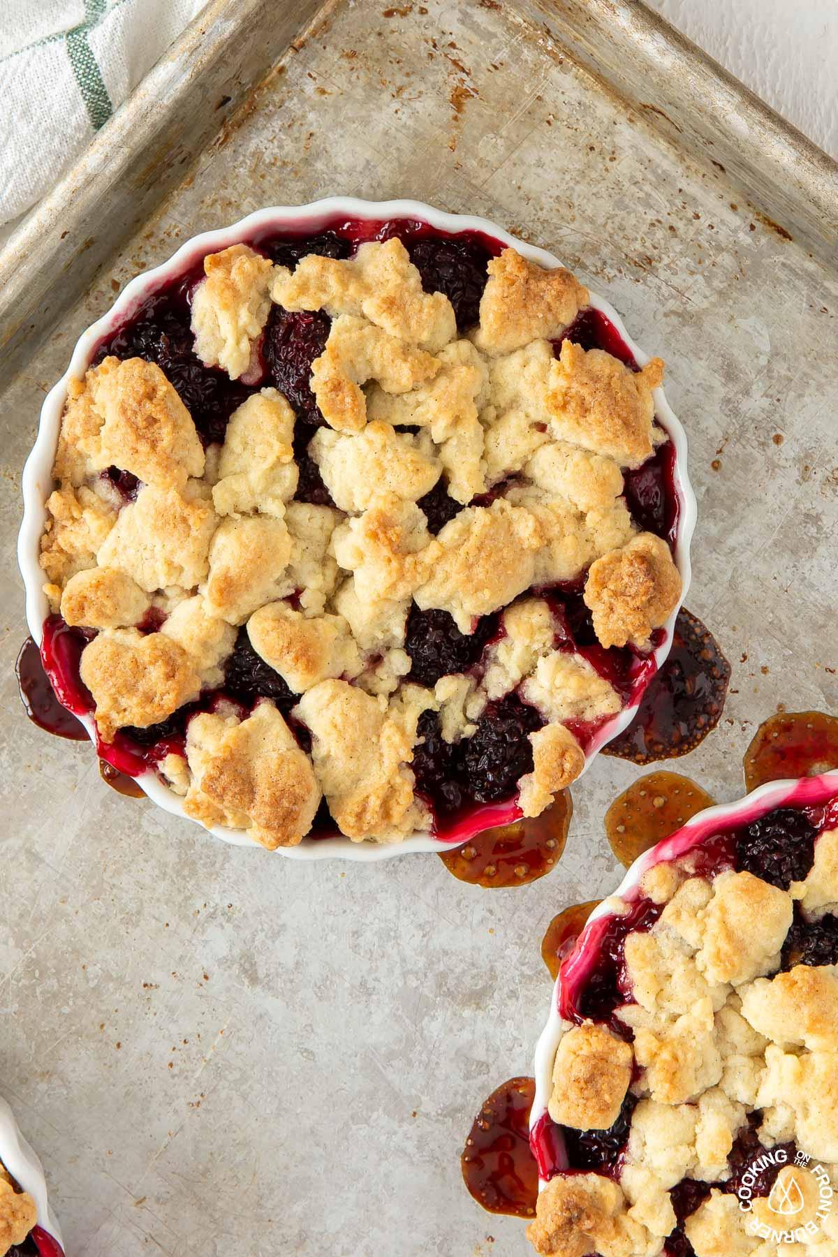 baked blackberry crumble tarts on a baking sheet