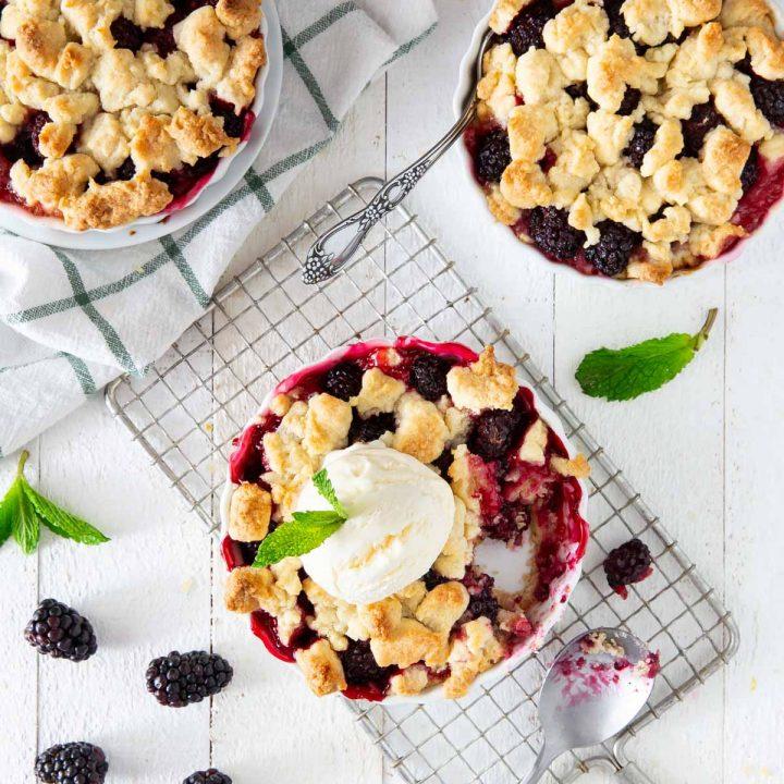 ice cream on top of a blackberry crumble tart