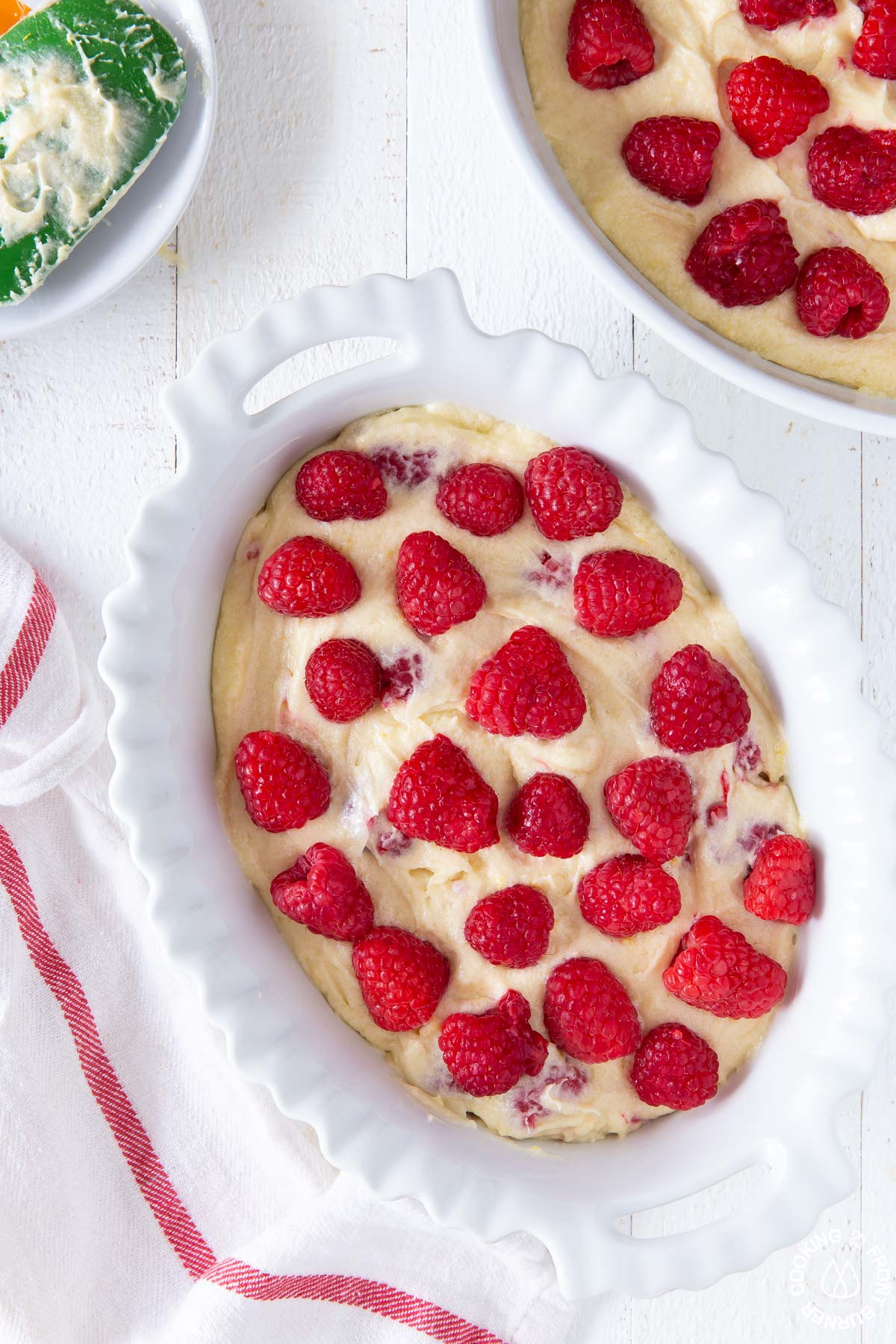 cake batter with adding raspberries on top