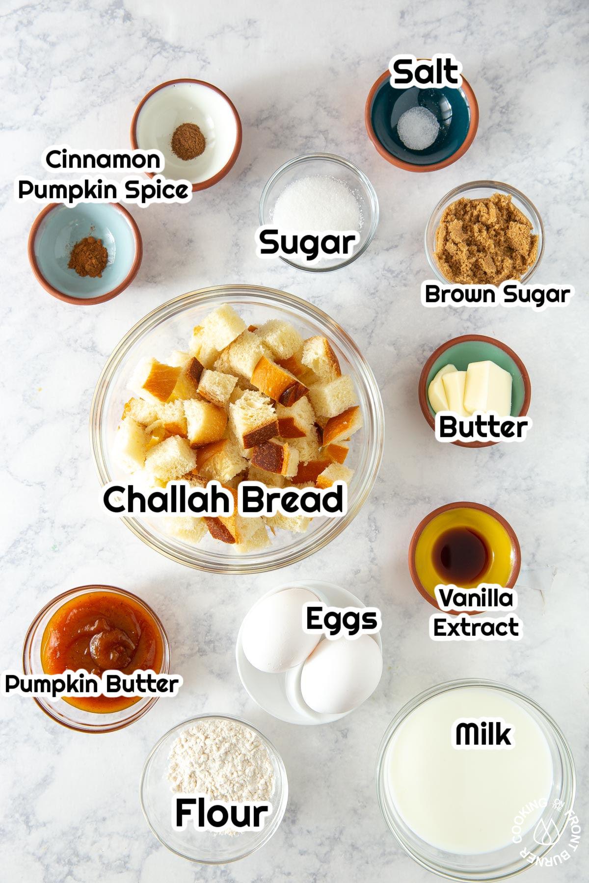 flour, sugar, vanilla, bread cubes, sugar,eggs in bowls on a board
